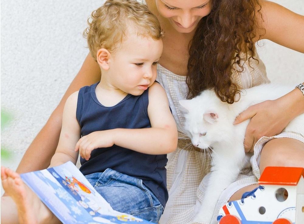 Matka trzyma dwuletniego chłopca i podchodzi do nich biały, mały kotek.