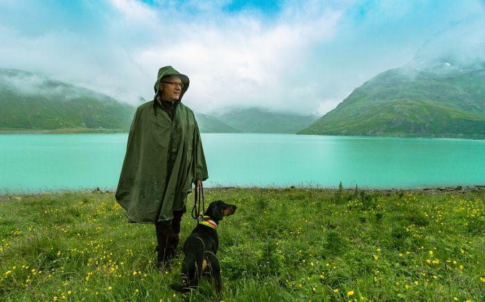 Mężczyzna z psem na brzegu jeziora.