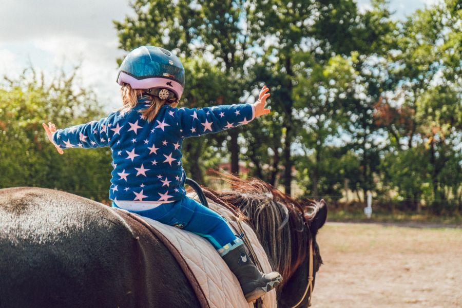 Dziecko podczas nauki jazdy konnej, ćwiczy równowagę podczas dosiadu.