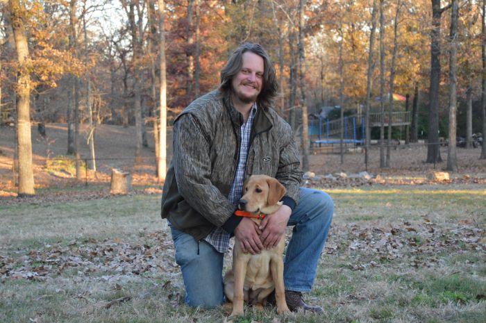 Mężczyzna siedzi z psem w parku