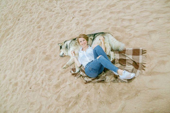 Kobieta leży przy psie na plaży.