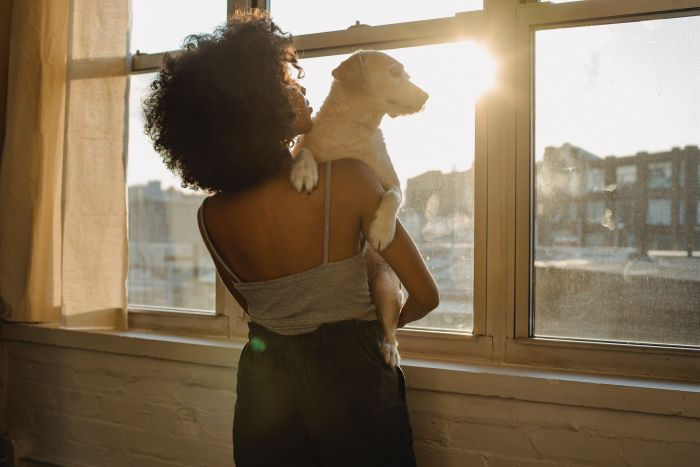 Kobieta z psem na rękach patrzą na zachód słońca.