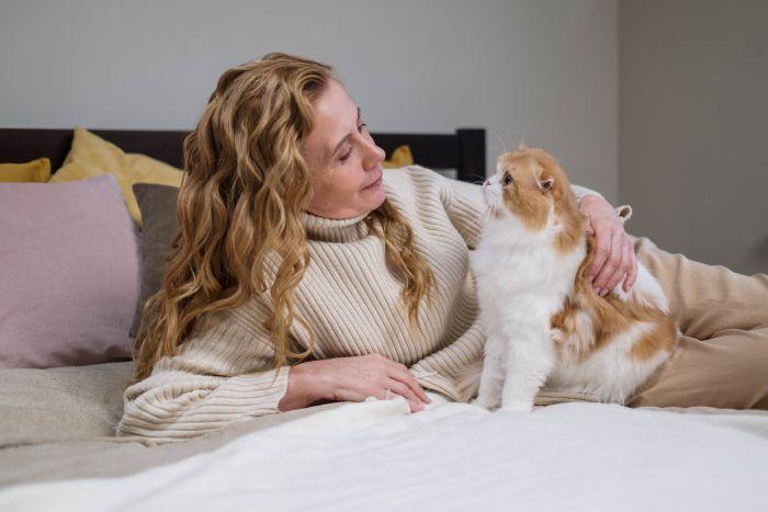 Kobieta z rudym kotem na łóżku