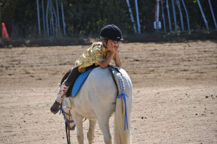 Dziewczynka siedzi tyłem na koniu.